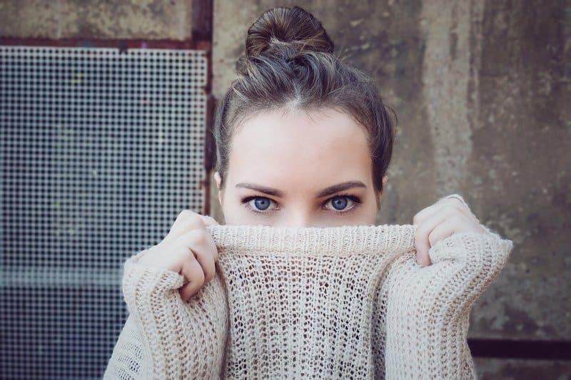 Frau bedeckt ihr Gesicht mit einem Pullover