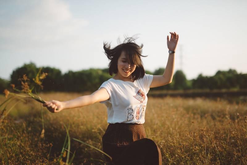 Frau, die Blume auf Feld hält