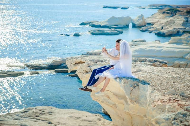 Frau, die Hochzeitskleid trägt, sitzt neben Mann auf der Steinspitze mit Blick auf das Meer