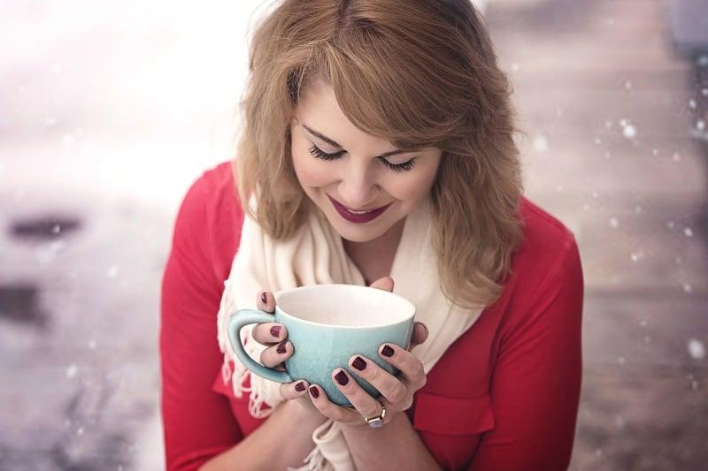 Frau die Kaffee im Schnee trinkt