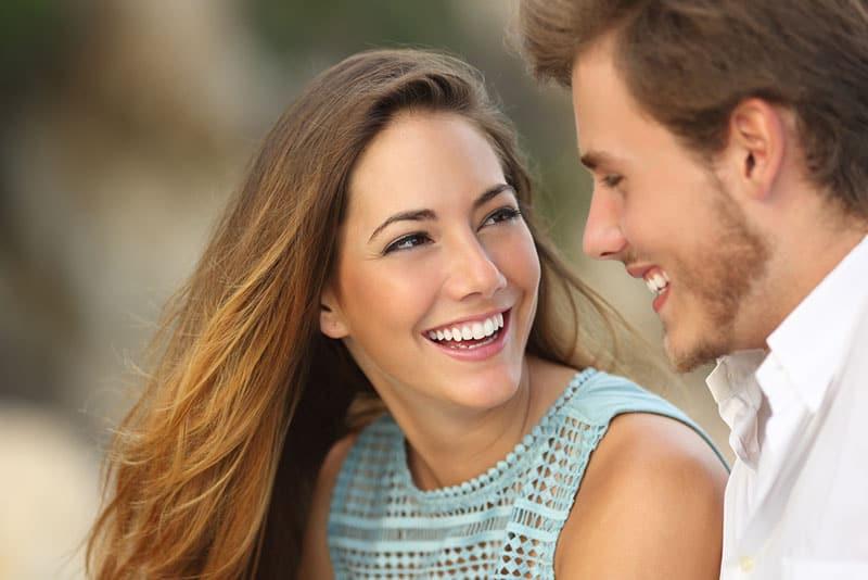 Frau, die Mann ansieht und lächelt