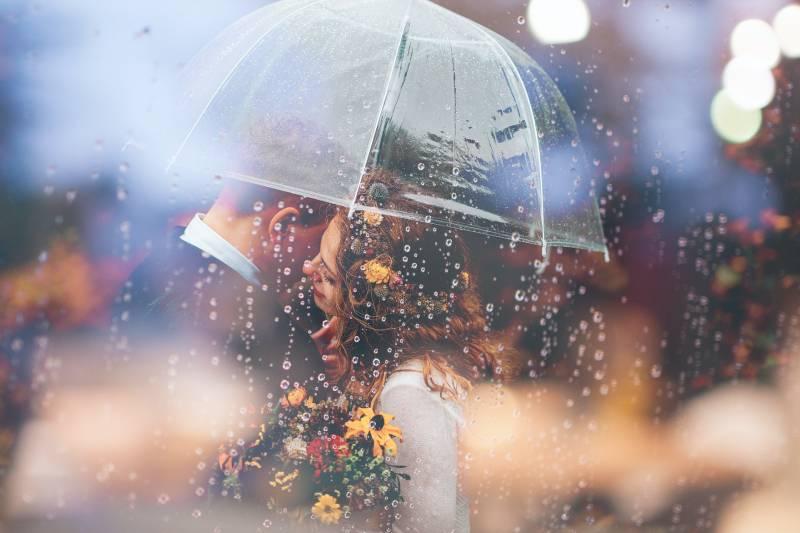 Frau, die Mann unter Regenschirm umarmt