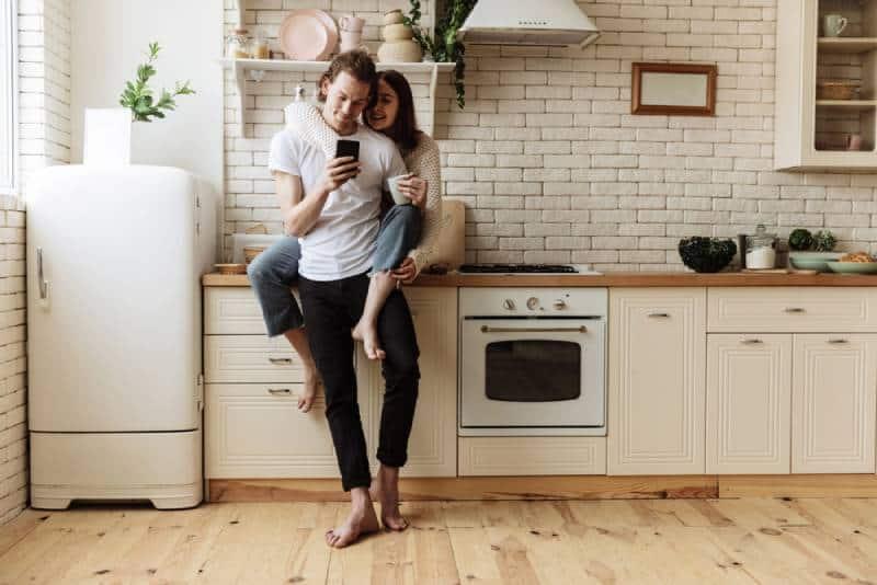 Frau, die Mann von hinten in der Küche umarmt