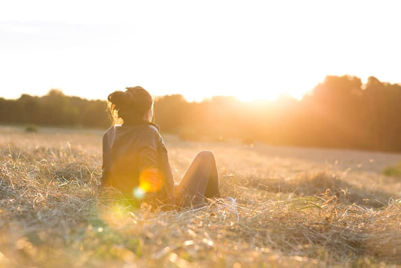 Frau, die Sonnenuntergang betrachtet