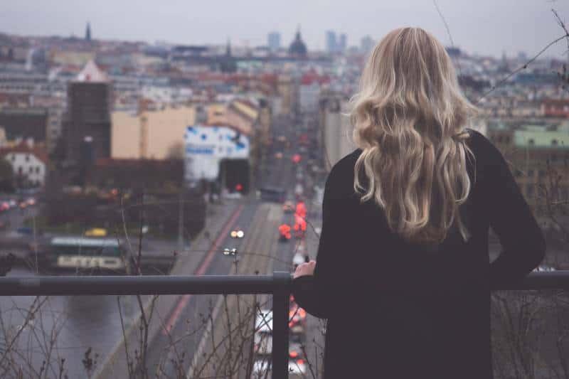 Frau, die Stadt vom Balkon betrachtet