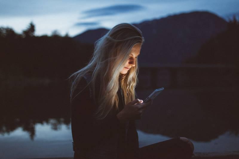 Frau, die am Abend am See eine SMS tippt