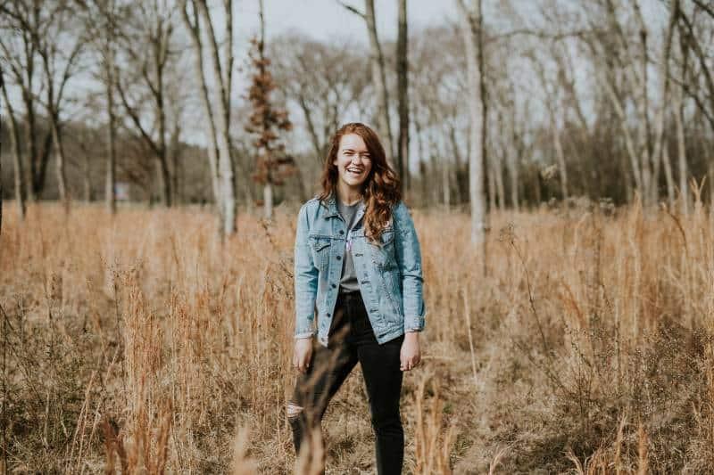 Frau, die am Wald beim Lächeln steht