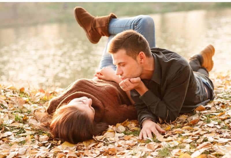 Frau, die auf Gras liegt, während Mann sie beobachtet