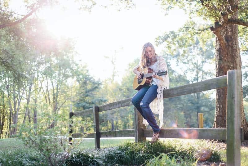 Frau, die auf Zaun sitzt, während sie Gitarre spielt