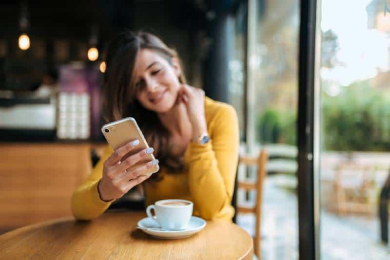 Frau, die auf ihrem Telefon im Café tippt