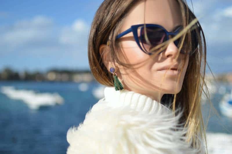 Frau, die blau gerahmte Cat-Eye-Sonnenbrille mit Gewässerhintergrund trägt