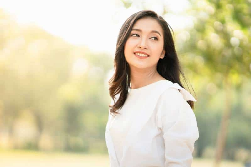 Frau, die das weiße Hemd im lässigen Stil draußen trägt