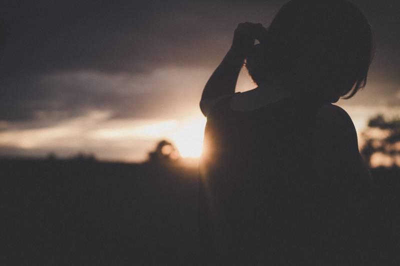 Frau, die draußen bei Sonnenuntergang steht