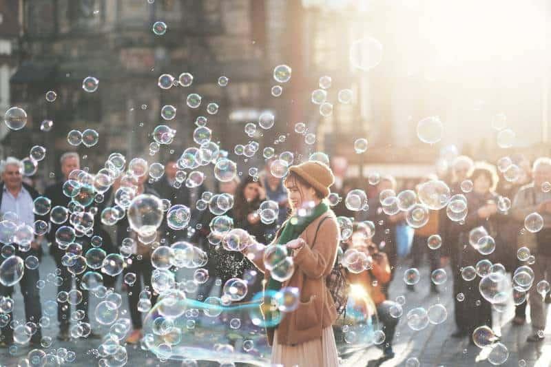 Frau, die draußen durch Blasen während des Tages umgeben steht