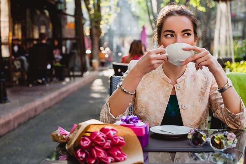 Frau, die draußen im Café Tee trinkt