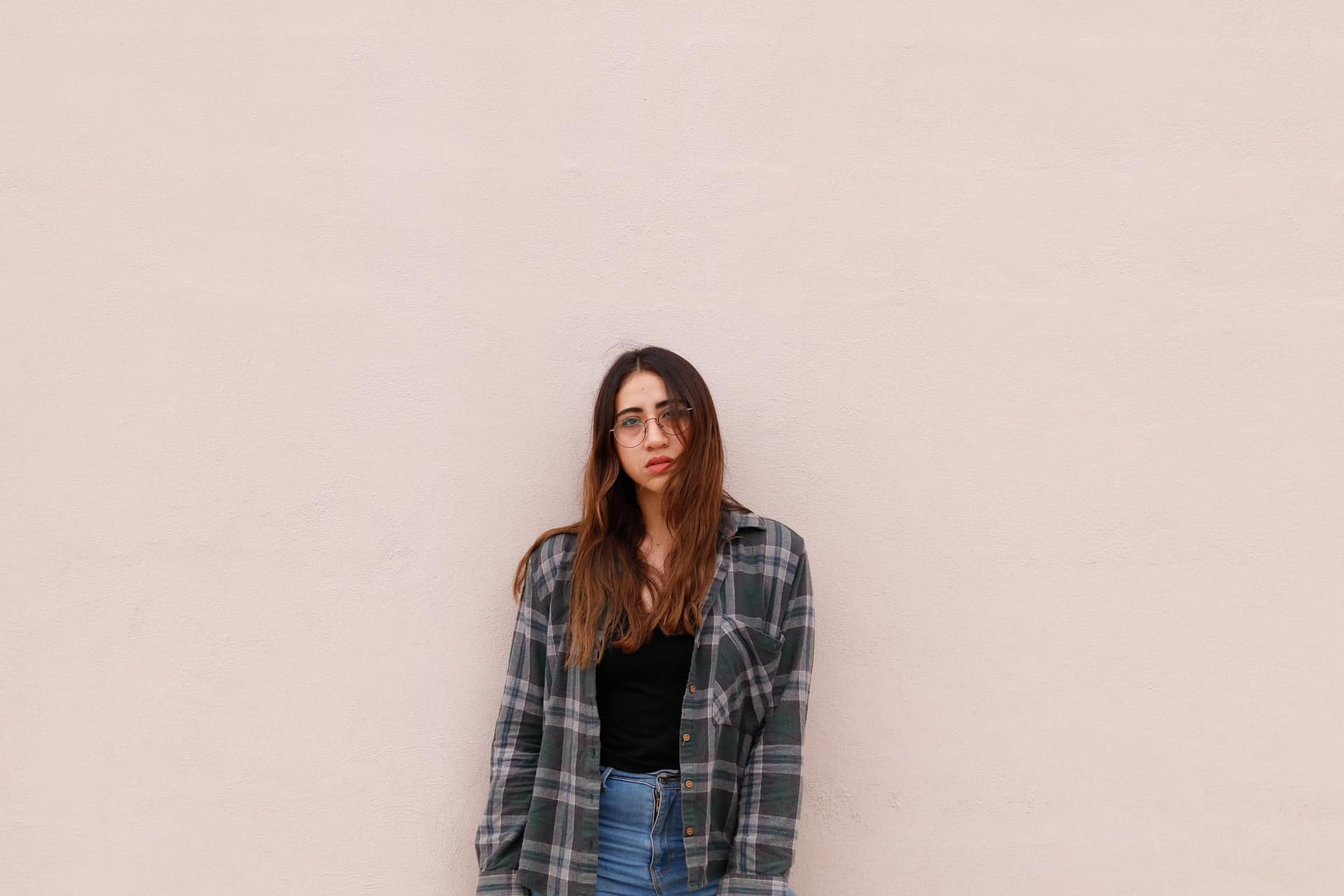 Frau, die graues Kleid trägt und vor Wand steht