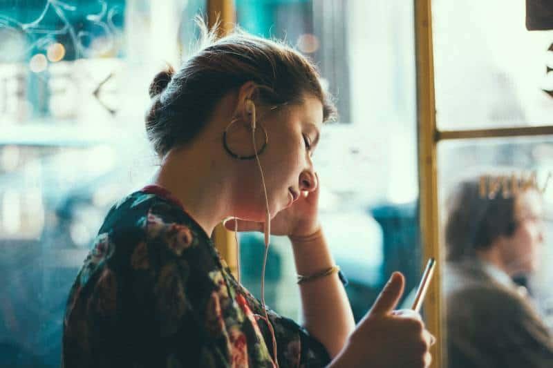 Frau, die ihr Telefon im Zug betrachtet