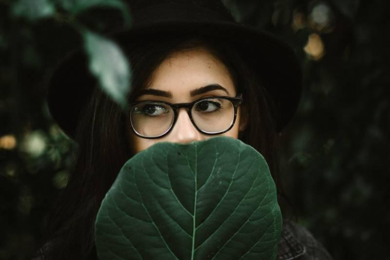 Frau, die ihren Mund mit Blatt bedeckt