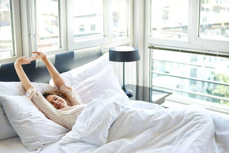 Frau, die mit erhobenen Armen im Bett streckt
