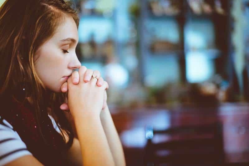 Frau, die mit geschlossenen Augen betet