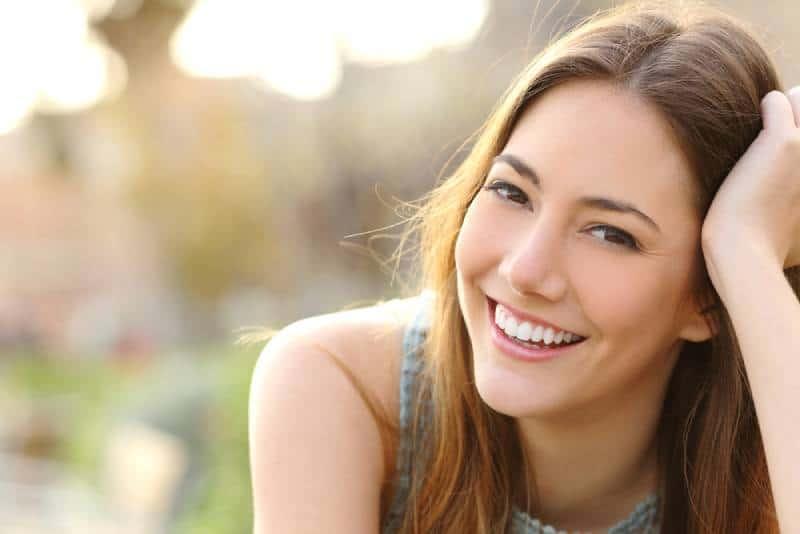 Frau, die mit perfektem Lächeln und weißen Zähnen in einem Park lächelt