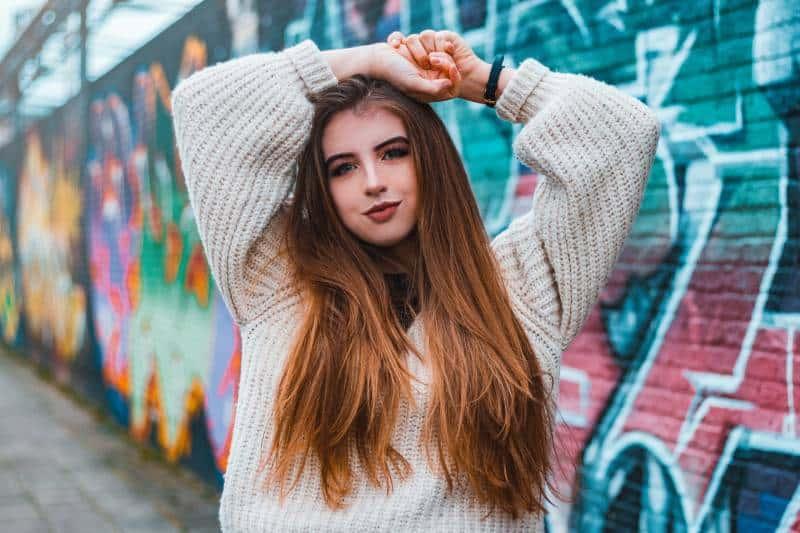 Frau, die nahe Graffitiwand aufwirft