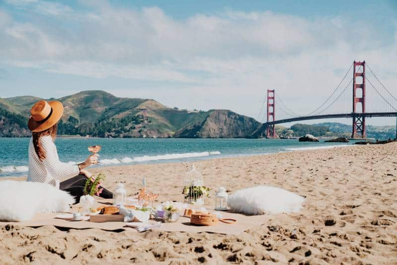 Frau, die nahe Küste sitzt, während sie Golden Gate, San Francisco betrachtet
