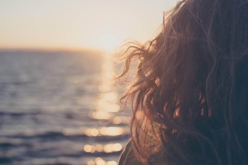 Frau, die nahe dem Gewässer während der goldenen Stunde steht