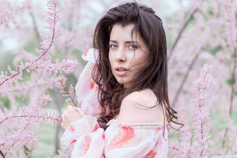 Frau, die nahe rosa Blattfeld steht