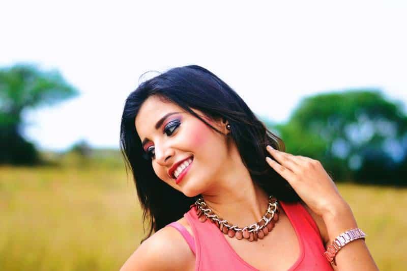 Frau, die rosa ärmellose Spitzen trägt, die beim Lächeln hervorstehen