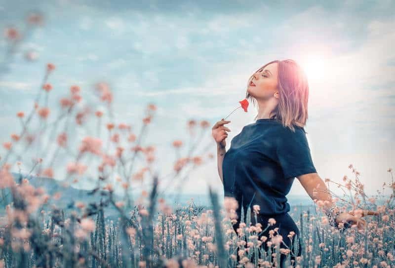 Frau, die rote Blume draußen hält