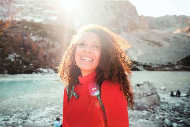 Frau, die rotes Rollkragenhemd nahe Berg trägt