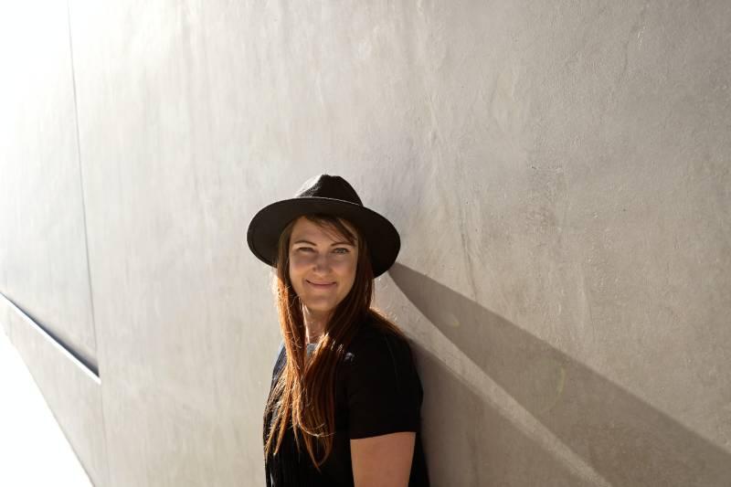 Frau, die sich auf weiße Betonwand stützt