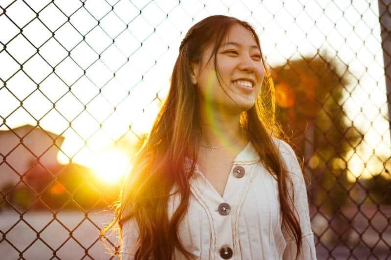 Frau, die vor Kettengliedzaun während der goldenen Stunde lächelt
