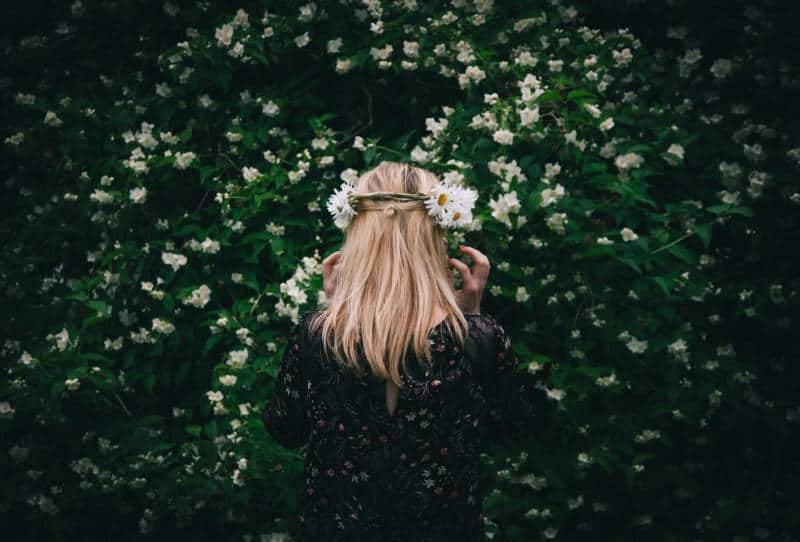 Frau, die vor weißen Blütenblättern steht