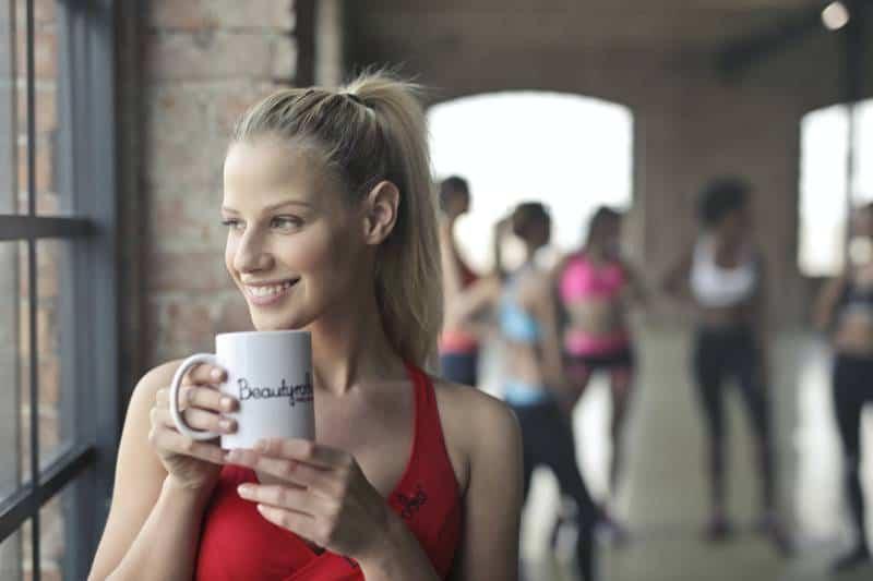 Frau, die weißen Keramikbecher beim Lächeln nahe Glasfenster hält