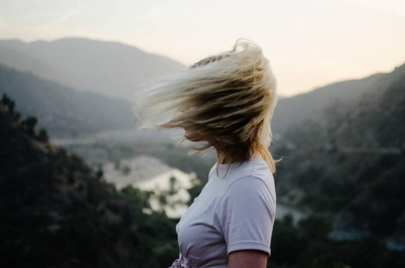 Frau, die weißes T-Shirt nahe Berg während des Tages trägt