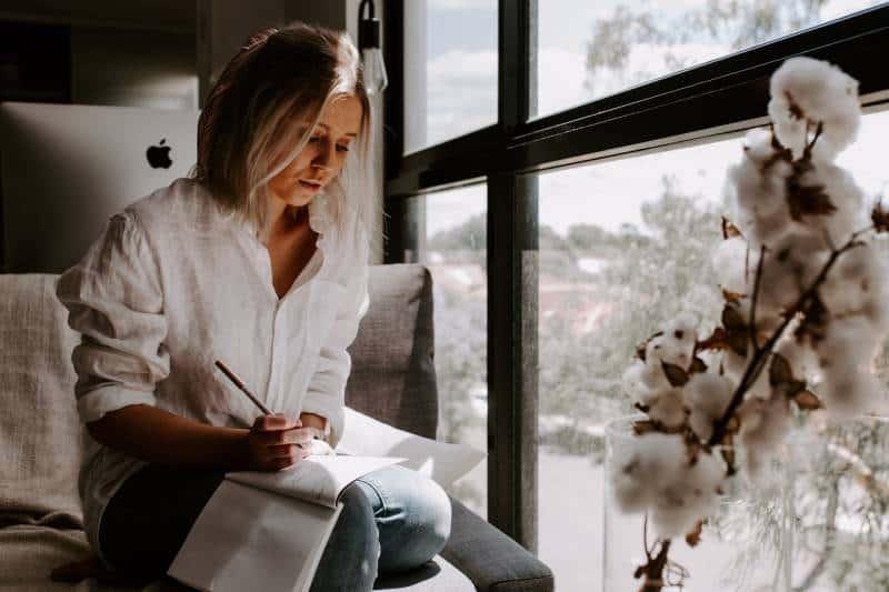 Frau, die zu Hause einen Brief schreibt