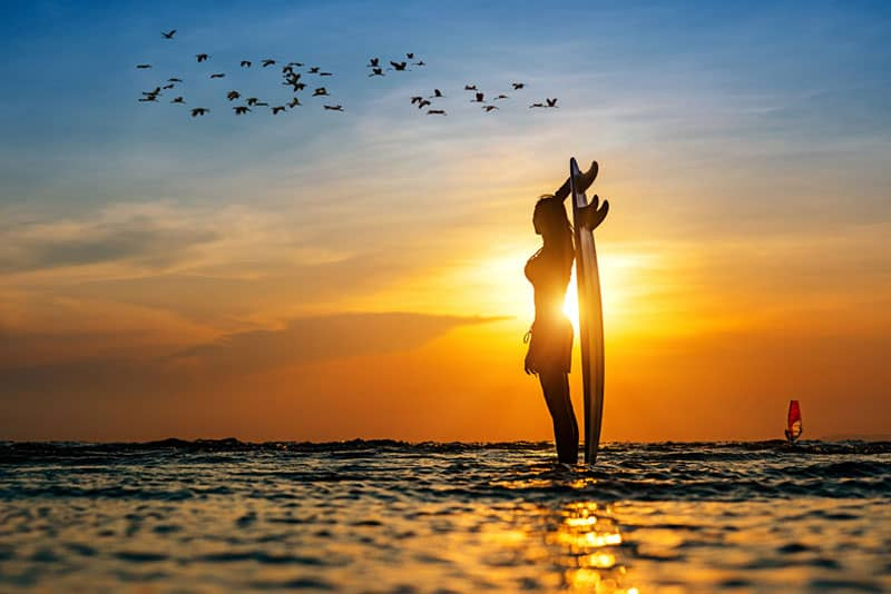 Frau hält Surfbrett auf dem Meer