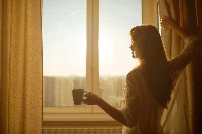 Frau hält eine Tasse mit heißem Tee und schaut auf den Sonnenaufgang