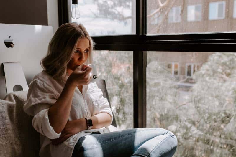 Frau hält eine weiße Tasse, die neben dem Fenster sitzt