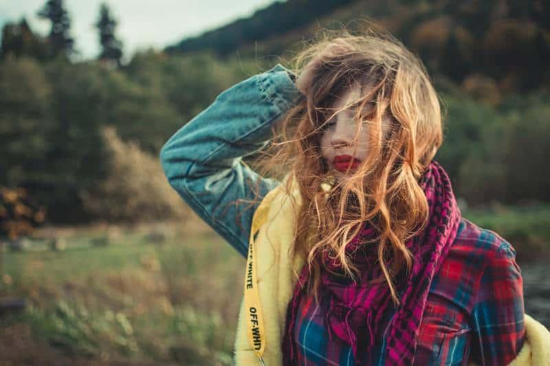 Frau hält ihre Haare gegen den Wind