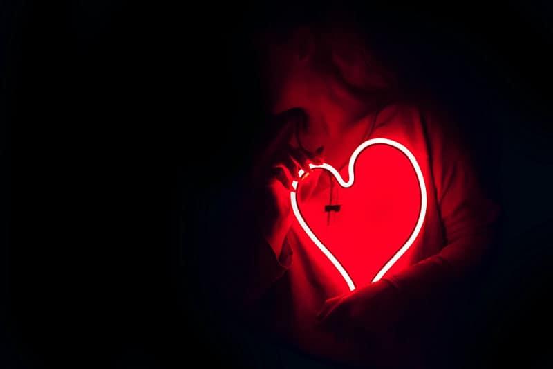 Frau hält leuchtendes Herz