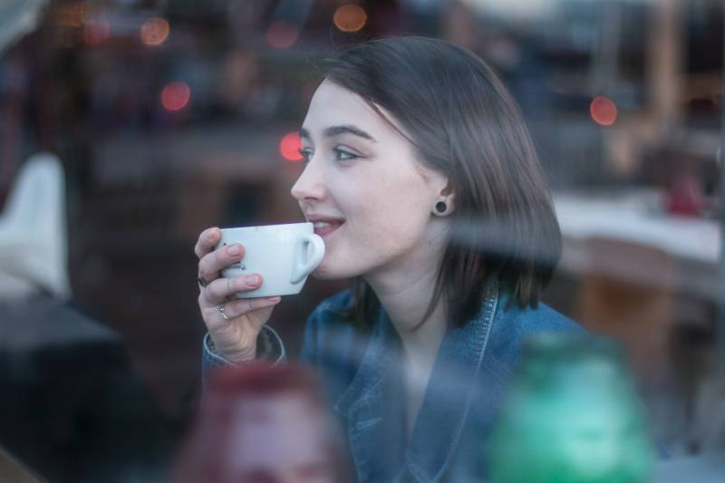 Frau hält weiße Keramik Teetasse