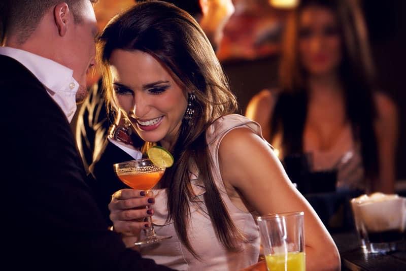 Frau hört Mann in der Bar