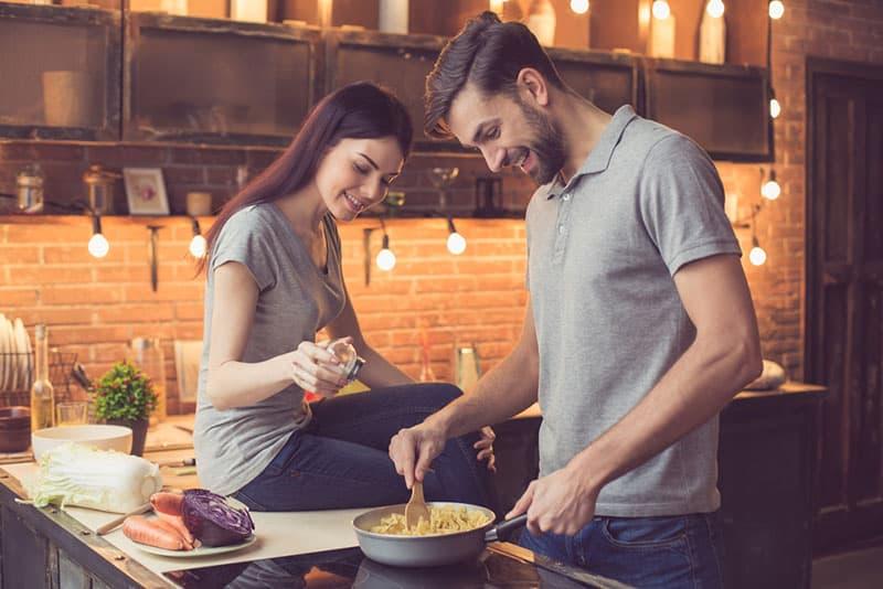 Frau hilft einem Mann beim Kochen