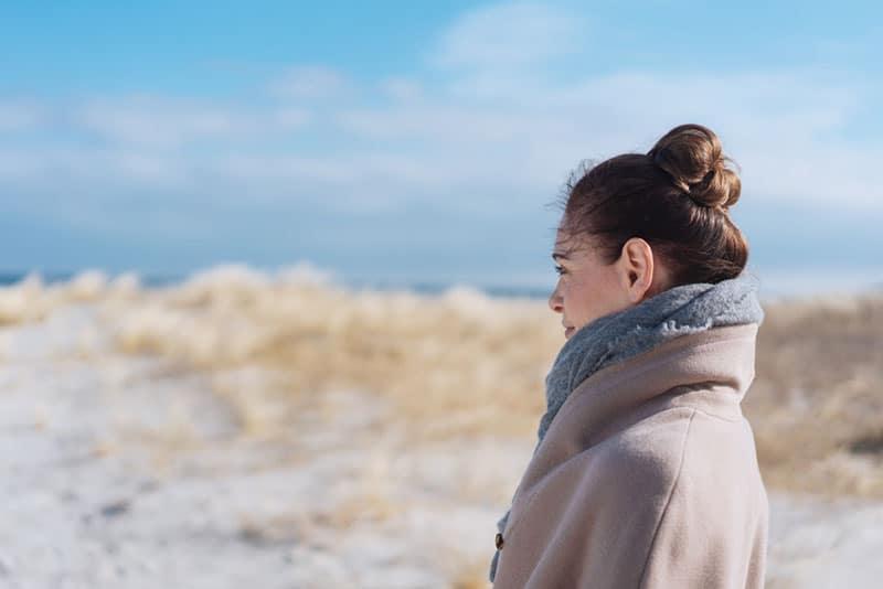 Frau im Mantel steht auf dem Sand