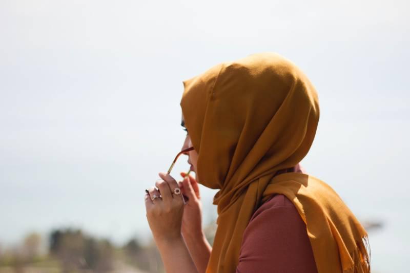 Frau im braunen Kopfschmuck, der Brillen in Tilt-Shift-Fotografie setzt