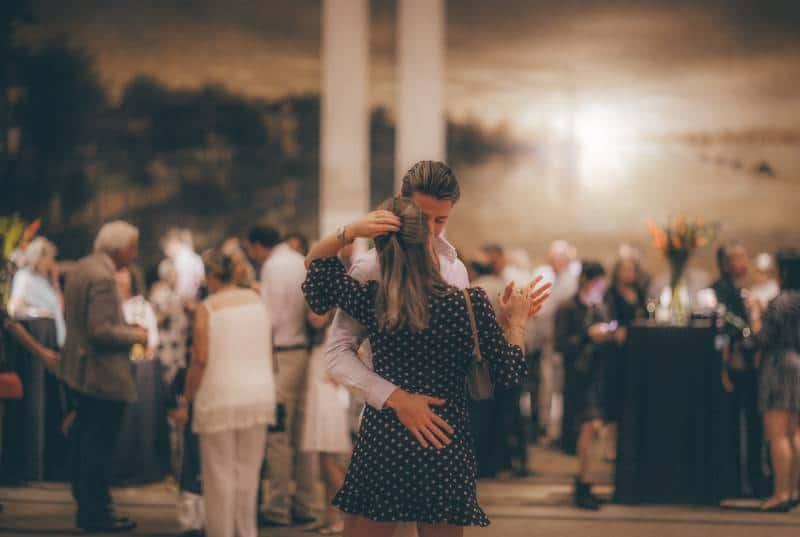 Frau im gepunkteten Kleid tanzt mit Mann im weißen Hemd