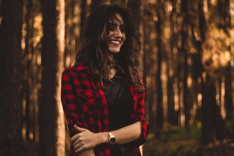 Frau im rot karierten Kleid vor Bäumen stehend